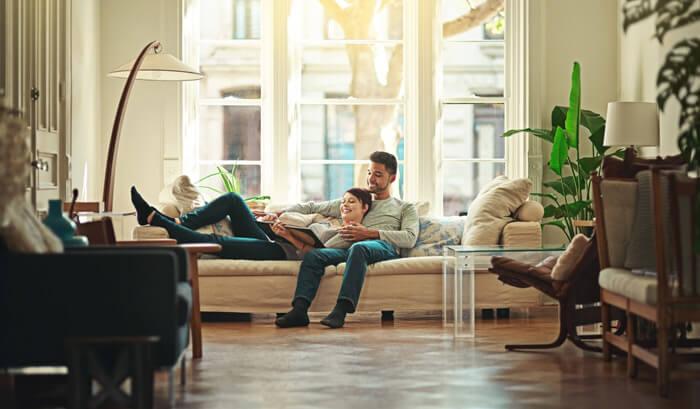 sala de estar com casal lendo no sofá