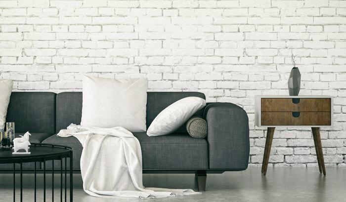sala de estar com sofá e parede de tijolinhos